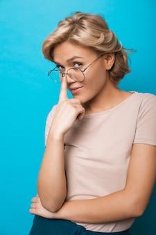 Chiuda sul ritratto di un'insegnante bionda caucasica che tocca i suoi occhiali mentre posa su una parete blu