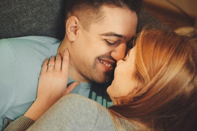 Chiuda sul ritratto delle coppie caucasiche che si baciano mentre giaceva sul divano