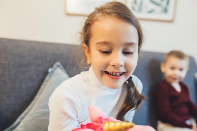 Close up ritratto di ragazza caucasica che mostra un giocattolo alla fotocamera con suo fratello sullo sfondo
