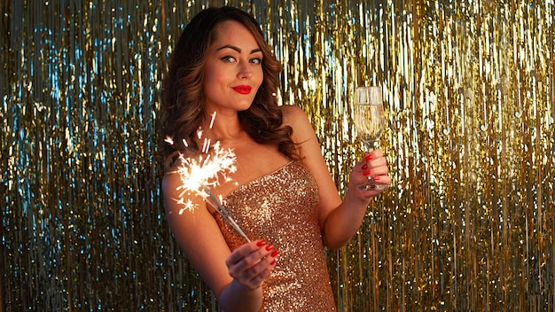 Close-up ritratto di donna caucasica in abito d'oro giovane donna beve champagne e azienda sparkler alla festa su sfondo oro brillante, messa a fuoco selettiva