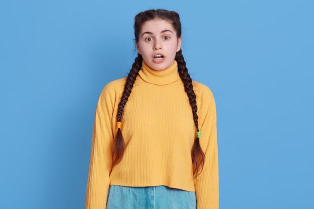 Close up ritratto di affascinante stupito stupito eccitato espressione allegra, signora con grandi occhi tenendo la bocca aperta, in posa isolata sopra la parete blu