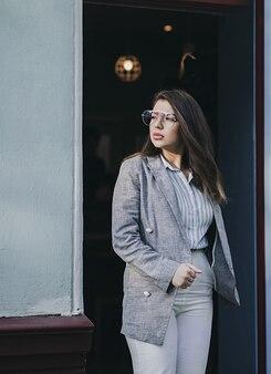 Ritratto del primo piano dell'affascinante ragazza bruna in giacca in posa vicino a street cafe