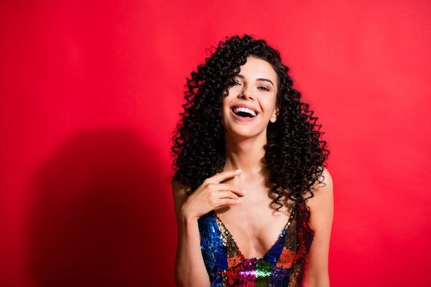 Ritratto ravvicinato di un'affascinante ragazza dai capelli ondulati allegra che si gode la celebrazione isolata su uno sfondo di colore rosso brillante