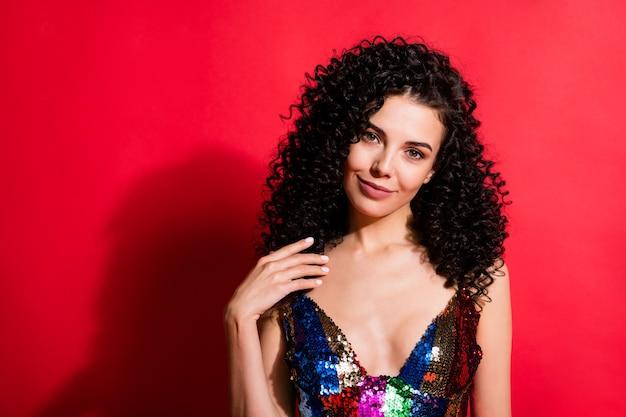 Ritratto ravvicinato di un'affascinante ragazza dai capelli ondulati allegra che indossa un abito da festa isolato su uno sfondo di colore rosso vibrante