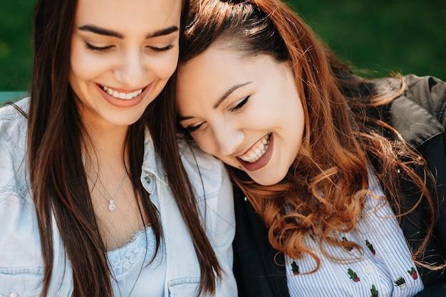Close up ritratto di un affascinante plus size donne con lunghi capelli ricci rossi che ride mentre si appoggia la testa sulla sua ragazza che sorride anche fuori.