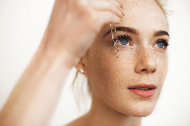 Close up ritratto di un'affascinante donna dai capelli rossi con le lentiggini che applicano siero ialuronico sul viso isolato su bianco.