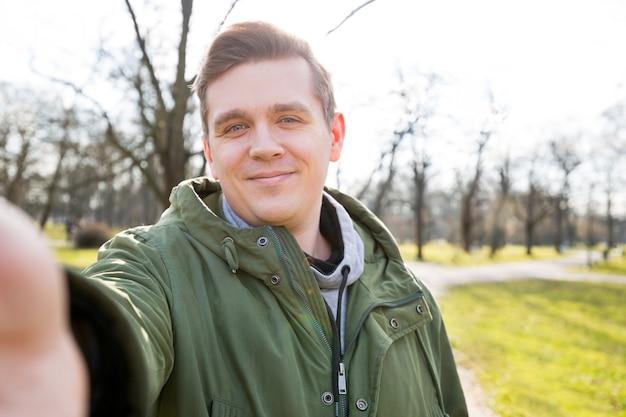 Chiuda sul ritratto di un uomo barbuto allegro che prende selfie sulla natura