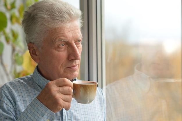 Ritratto del primo piano dell'uomo maturo allegro a casa con tè