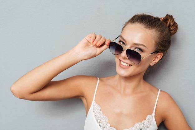 Chiuda sul ritratto di una donna abbastanza giovane allegra che tiene gli occhiali da sole e che guarda l'obbiettivo isolato su uno sfondo grigio
