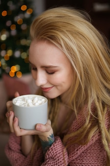 Ritratto del primo piano di una ragazza sorridente allegra con i dreadlocks con una tazza di cacao con marshmallow