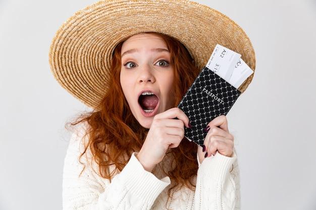 Close up ritratto di una allegra giovane ragazza adolescente che indossa cappello estivo in piedi isolato su sfondo bianco, mostrando il passaporto con i biglietti aerei