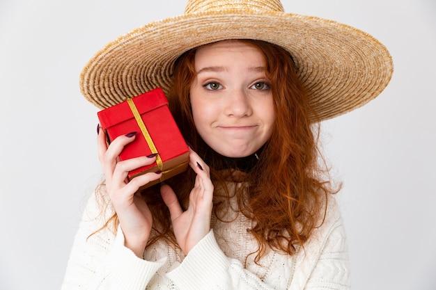 Primo piano ritratto di una giovane ragazza adolescente allegra che indossa cappello estivo in piedi isolato su sfondo bianco, mostrando la casella attuale