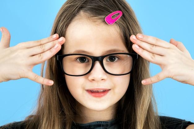 Chiuda sul ritratto di una ragazza della scuola del bambino che indossa gli occhiali isolati sulla parete blu.