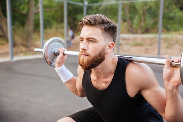 Ritratto ravvicinato di un uomo sportivo barbuto concentrato che fa esercizi di squat con bilanciere all'aperto