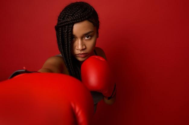 Ritratto ravvicinato di un giovane pugile sportivo africano concentrato che indossa guanti da boxe rossi, facendo colpo diretto, isolato su sfondo rosso con spazio di copia. pugile donna nera che prende a pugni verso la telecamera