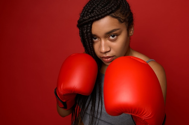 Ritratto ravvicinato di un giovane pugile sportivo africano concentrato che indossa guanti da boxe rossi, facendo colpo diretto, isolato su sfondo rosso con spazio di copia. donna giovane atleta durante l'allenamento cardio