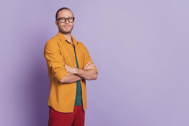 Ritratto ravvicinato di un giovane fiducioso con le braccia piegate sul muro viola