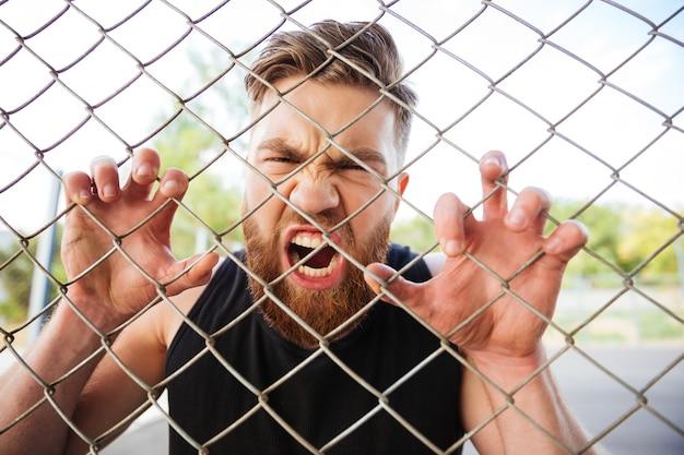 Ritratto ravvicinato di un uomo barbuto pazzo che grida con le mani su una recinzione metallica all'aperto