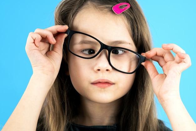 Chiuda sul ritratto di una ragazza della scuola del bambino dagli occhi incrociati che indossa i vetri di sguardo isolati sulla parete blu