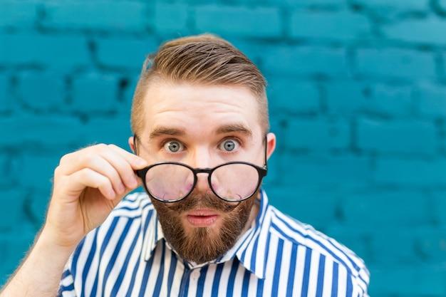 Ritratto del primo piano di un giovane sorpreso curioso in bicchieri con i baffi e la barba in posa su un muro di muro di mattoni sfocato blu. concetto di sorpresa e informazioni scioccanti. copyspace