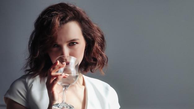 Il ritratto del primo piano della donna adulta sveglia tiene il bicchiere d'acqua, beve e guarda la telecamera su sfondo scuro. foto domestica della femmina con acqua fresca. concetto di regolazione del bilancio idrico e dissetante