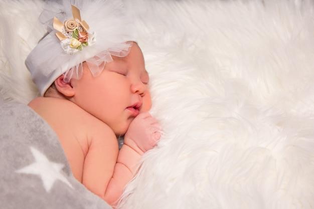 Ritratto ravvicinato di un neonato addormentato carino e copia spazio su una coperta di pelliccia bianca