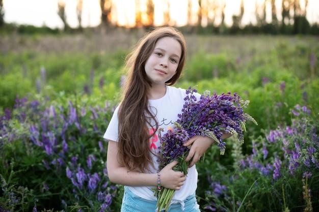 Ritratto del primo piano della ragazza carina in un campo di lupini.