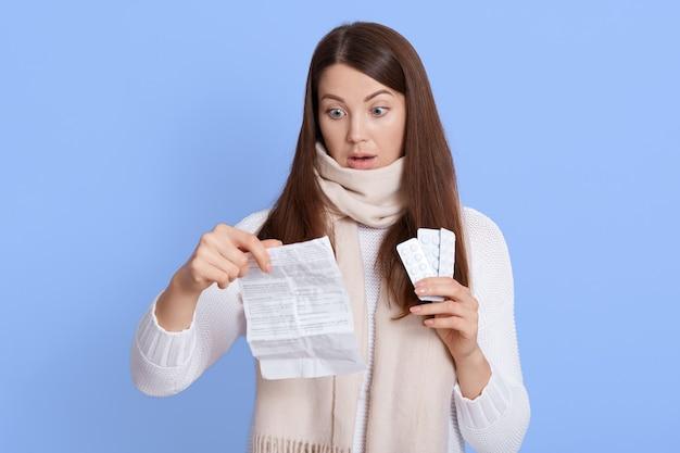 Chiuda sul ritratto della signora triste delusa che tiene le pillole e le sue istruzioni nelle mani, pensando di assumere droghe, guardando la carta con la bocca ampiamente aperta e l'espressione facciale scioccata.