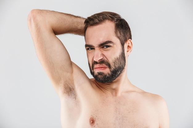 Close up ritratto di un uomo barbuto disgustato in piedi isolato su bianco, annusando la sua ascella