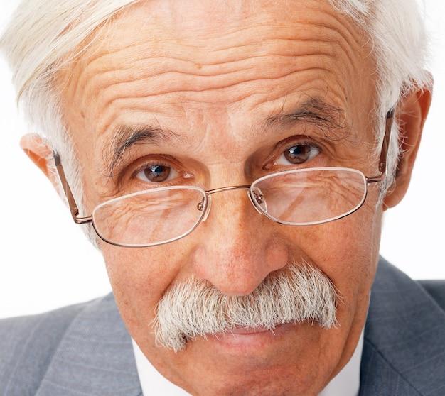 Ritratto del primo piano di un uomo d'affari anziano nei vetri che ti guarda