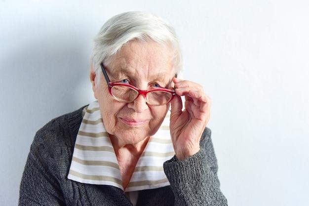 Ritratto del primo piano di un'anziana donna dai capelli grigi con gli occhiali.