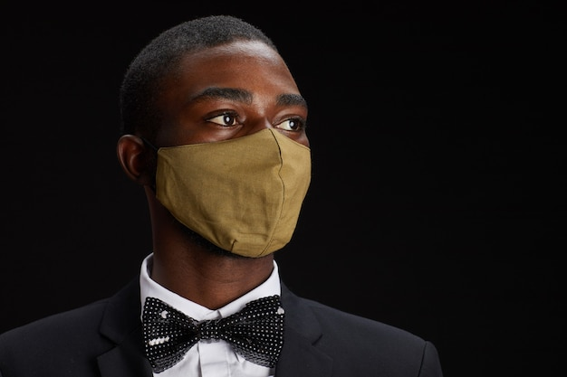 Close up ritratto di elegante uomo afro-americano che indossa la maschera per il viso mentre posa su sfondo nero alla festa, copia dello spazio