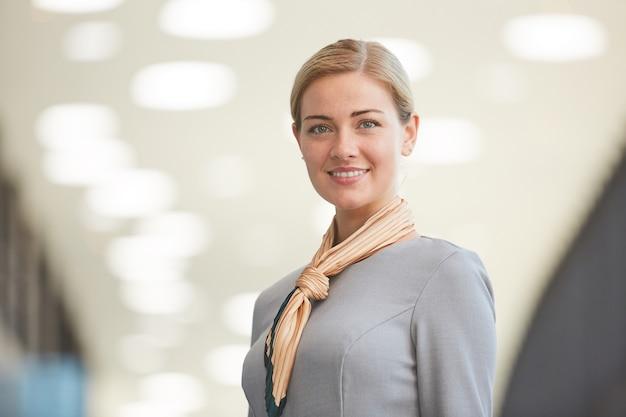 Close up ritratto di elegante bionda assistente di volo e sorridente mentre posa in aeroporto,