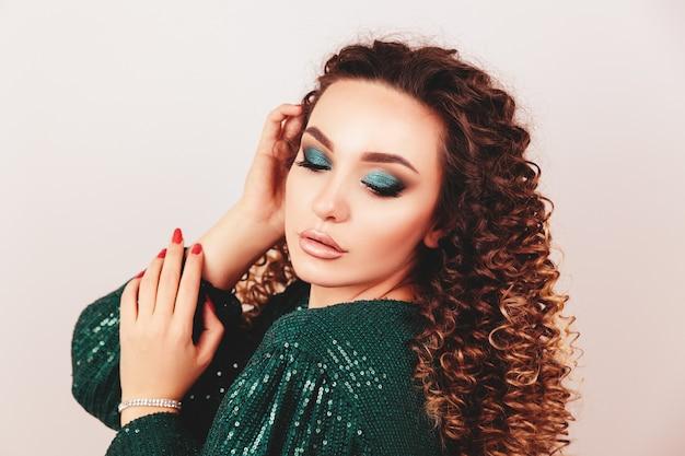 Chiuda sul ritratto della donna lussuosa elegante in abito da sera con paillettes verde alla moda. elegante acconciatura ondulata, trucco luminoso, unghie rosse. concetto di bellezza