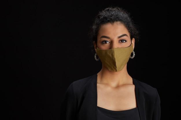 Close up ritratto di elegante donna mediorientale che indossa la maschera per il viso mentre posa su sfondo nero alla festa, copia dello spazio