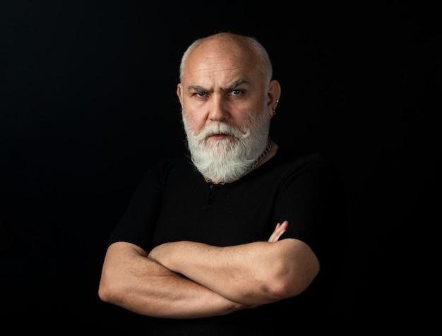 Close up ritratto di un elegante uomo anziano con i capelli grigi isolati su sfondo nero. fiducioso serio uomo anziano con le braccia conserte.