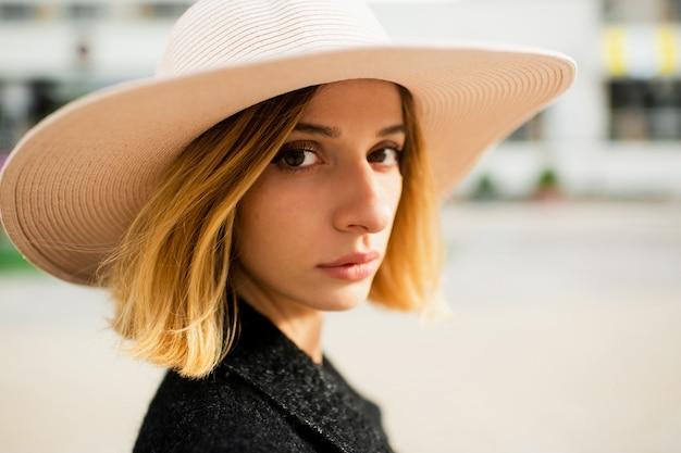 Chiuda sul ritratto della donna bionda alla moda elegante dei capelli corti