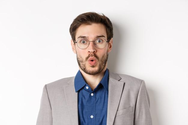 Primo piano ritratto di impiegato eccitato in occhiali e vestito dicendo wow, fissando stupito la fotocamera, in piedi su sfondo bianco.