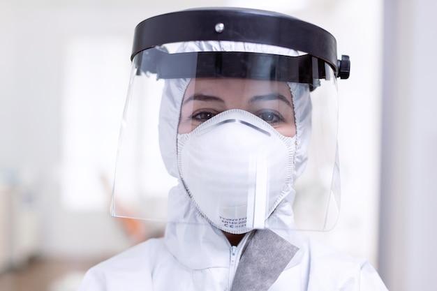 Ritratto ravvicinato di medico esausto con visiera e maschera facciale contro la lotta con il coronavirus. personale medico vestito con dispositivi di protezione contro l'infezione da covid-19 durante la pandemia globale