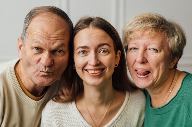 Close up ritratto di famiglia con anziani donna matura, uomo e figlia millenaria.