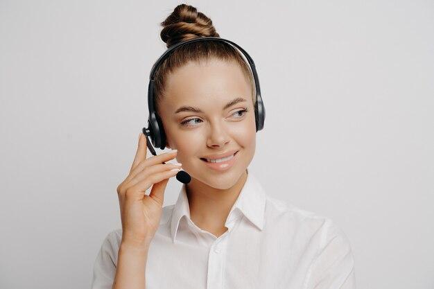 Primo piano ritratto di lavoratrice di banca in camicia bianca e capelli in chignon, parlando su auricolare nero, raccontando informazioni sui clienti e guardando da parte con un sorriso isolato su sfondo grigio
