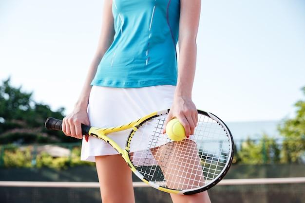 Ritratto ravvicinato di gambe femminili con racchetta da tennis e palla sul campo