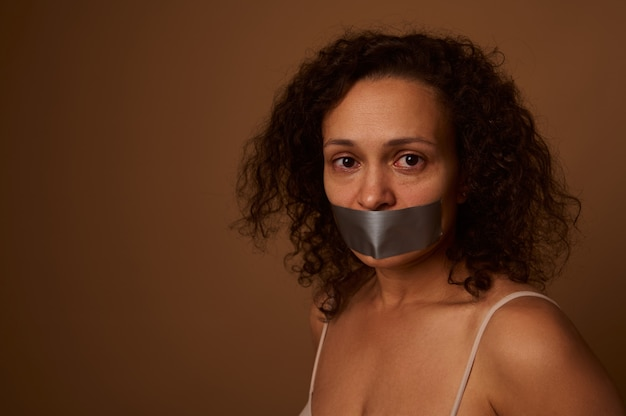 Ritratto ravvicinato. donna africana disperata spaventata con le lacrime agli occhi, bocca sigillata che guarda l'obbiettivo con disperazione, fondo beige scuro isolato. concetto di stop alla violenza contro le donne