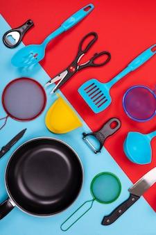 Chiuda sul ritratto della padella con l'insieme degli utensili della cucina su rosso-blu