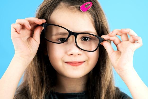 Chiuda sul ritratto di una ragazza divertente della scuola del bambino che indossa i vetri di sguardo isolati su fondo blu.