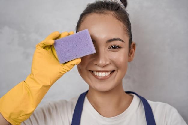 Ritratto ravvicinato di una donna delle pulizie divertente in guanti di gomma gialli che coprono un occhio con una spugna da cucina, che guarda l'obbiettivo e sorride, in piedi contro il muro grigio. pulizie, servizi di pulizia