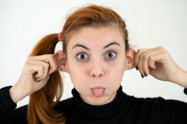 Chiuda sul ritratto della ragazza divertente che tiene le sue orecchie e che attacca fuori la lingua come una scimmia.