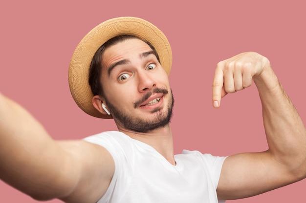 Chiuda sul ritratto di giovane blogger hipster barbuto bello divertente in camicia bianca e cappello casual in posa e facendo selfie sul telefono, puntare il dito verso il basso. al coperto, isolato, girato in studio, sfondo rosa