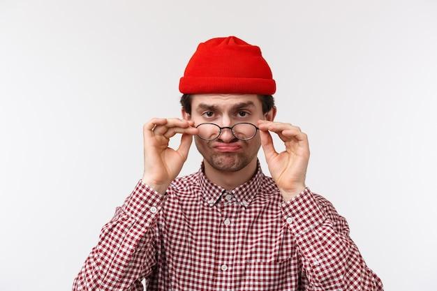 Close-up ritratto divertente scettico maschio caucasico in hipster beanie, guarda da sotto la fronte