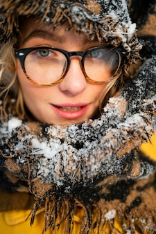 Chiuda sul ritratto di ragazza divertente giovane hipster con gli occhiali e la sciarpa che copre la testa